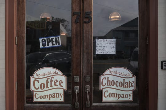 Apalachicola Coffee and Chocolate Company posts changes to their hours following Hurricane Michael in downtown Apalachicola, Fla. Thursday, Oct. 25, 2018, just two weeks after Hurricane Michael hit the coastal town.