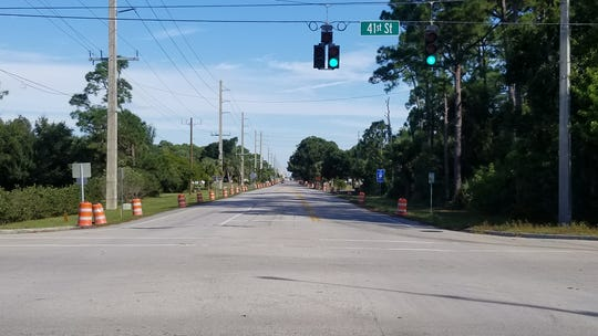 Traffic barrels line the sides of 58th Avenue north of 41st Street as city officials prepare to close off another stretch of 58th Ave for road improvements.