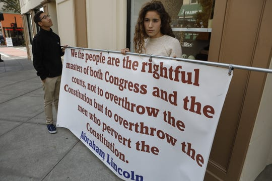 Trey Sanabria, 16, and Lea Spatz, 17, both of Valley Cottage, hold a banner that is in the center of controversy in Nyack on Oct. 26, 2018.
