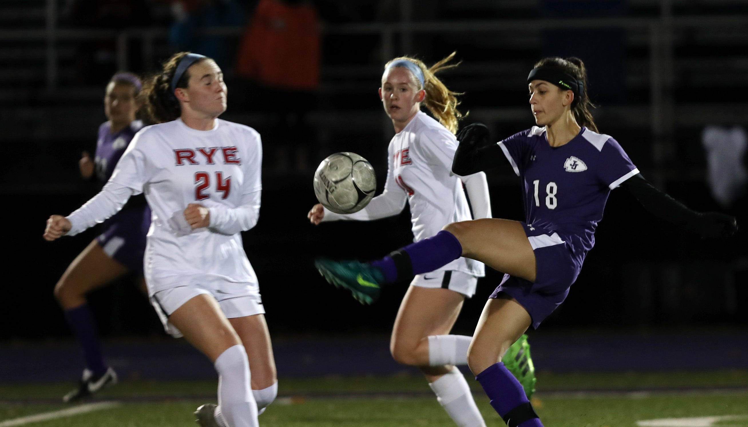From right, John Jay's Adeline Angelino (18) clears the ball away from Rye's Molly Broderick (24) during girls soccer playoffs at John Jay High School in Cross River Oct. 25, 2018. John Jay won the game 2-1 in double overtime.