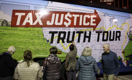 """Attendees at a stop on the 'Nuns on the Bus' """"Tax Justice Truth Tour"""" in Wilmington sign the bus after hearing the nuns urge change in Trump tax policies."""