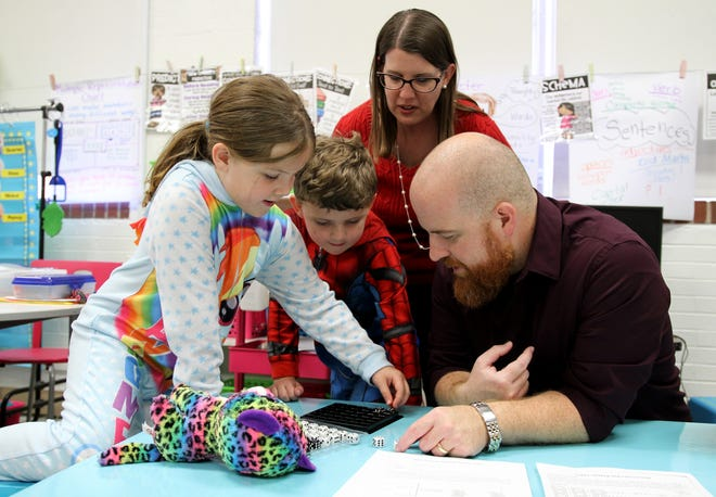 Addie Arnold, left, her brother Aaron and parents Loriw and Brandon play a math game with dice during S.T.E.A.M Night Thursday, Oct. 25, 2018, at Cunningham Elementary.
