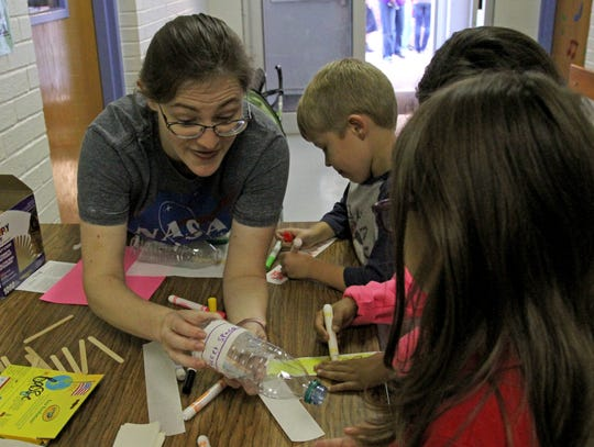 Liz Farr helps students make bottle rockets during S.T.E.A.M Night Thursday, Oct. 25, 2018, at Cunningham Elementary.