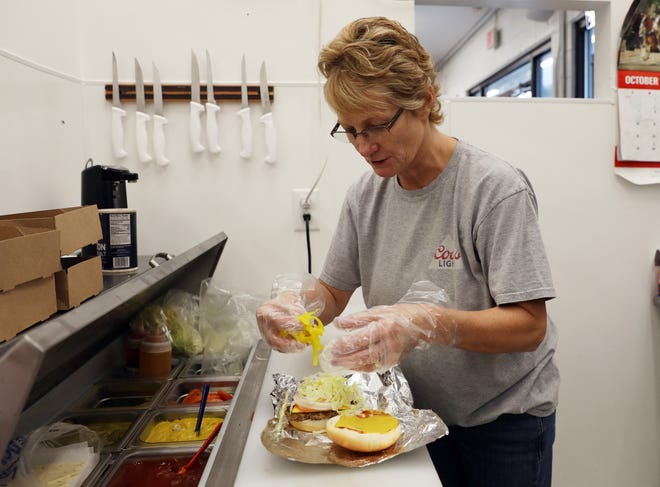 Mary Phillis, manager at West Side Market, readies a breakfast sandwich, which is just one of hundreds she would serve during the day.