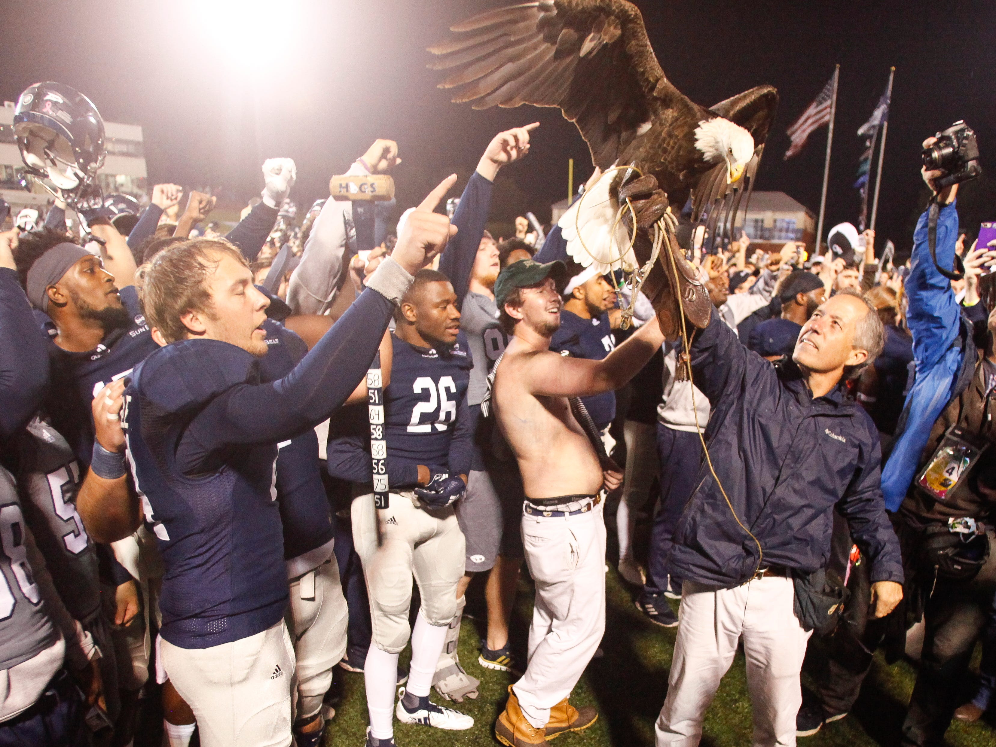 The Georgia Southern Eagles celebrate their win over Appalachian State as handler Steve Hein hoists Freedom, the team's live mascot, in Statesboro, Georgia.