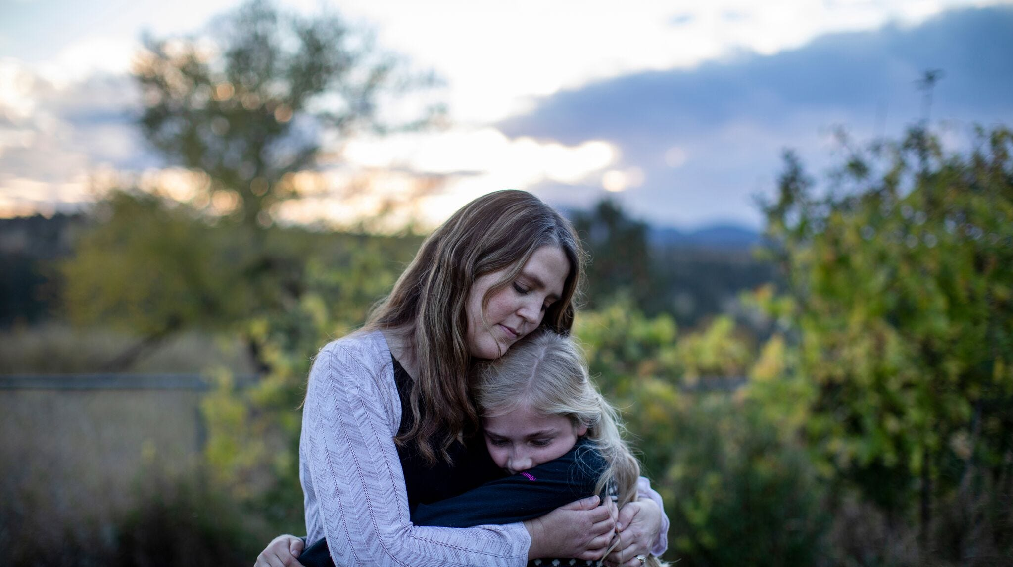 Kristen  Kilmer  hugs  her  12-year-old  daughter  at  their  home  in  Spearfish,  South Dakota. Kilmer has relied on precision medicine to treat her breast cancer, but the approach is expensive, and there are no guarantees her insurer will keep covering it.