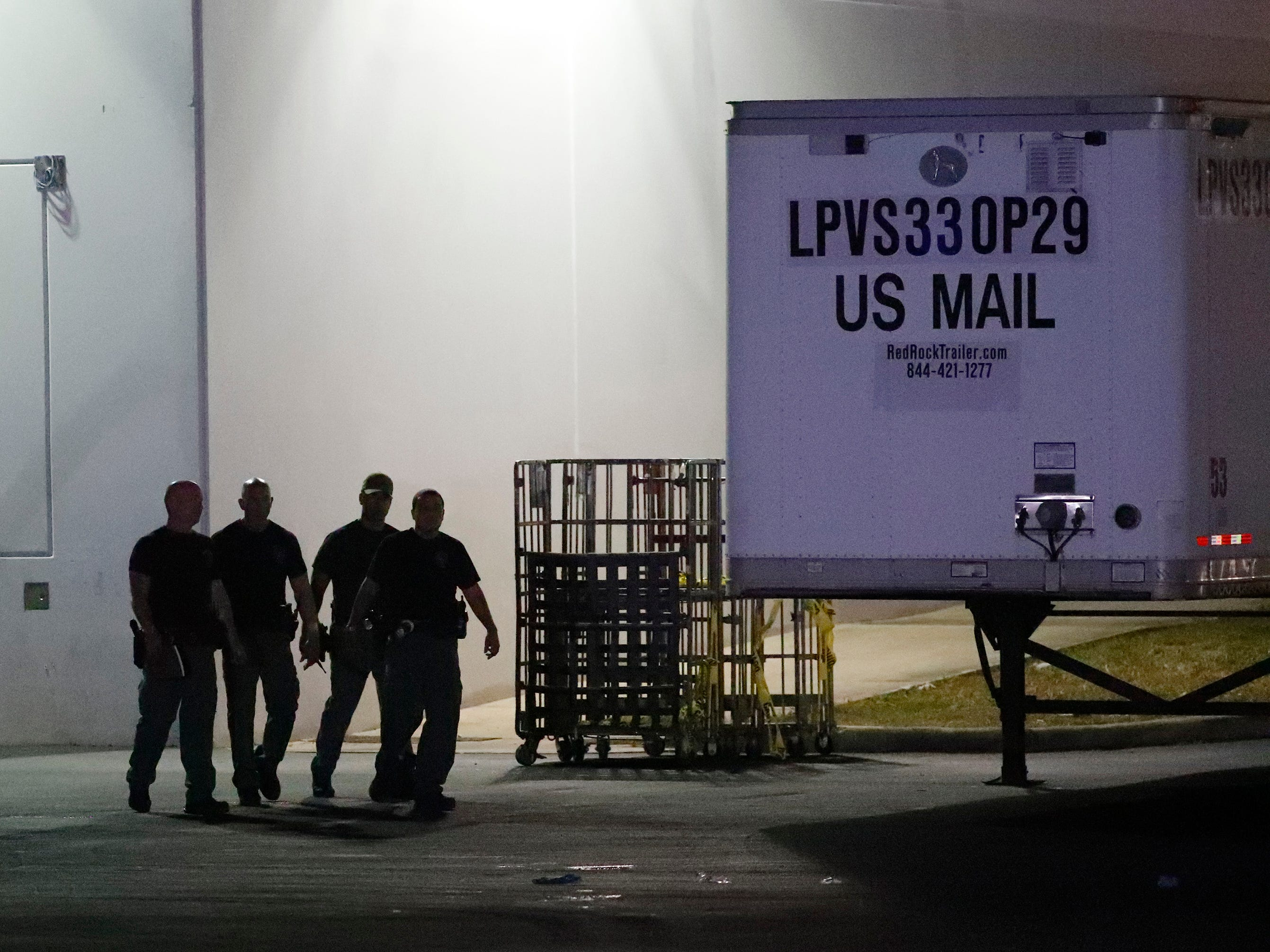 Members of the Miami-Dade County Bomb Squad walk outside a postal facility, Oct. 25, 2018, in Opa-locka, Fla. Investigators searched coast-to-coast Thursday for the culprit and motives behind the bizarre mail-bomb plot aimed at critics of the president.