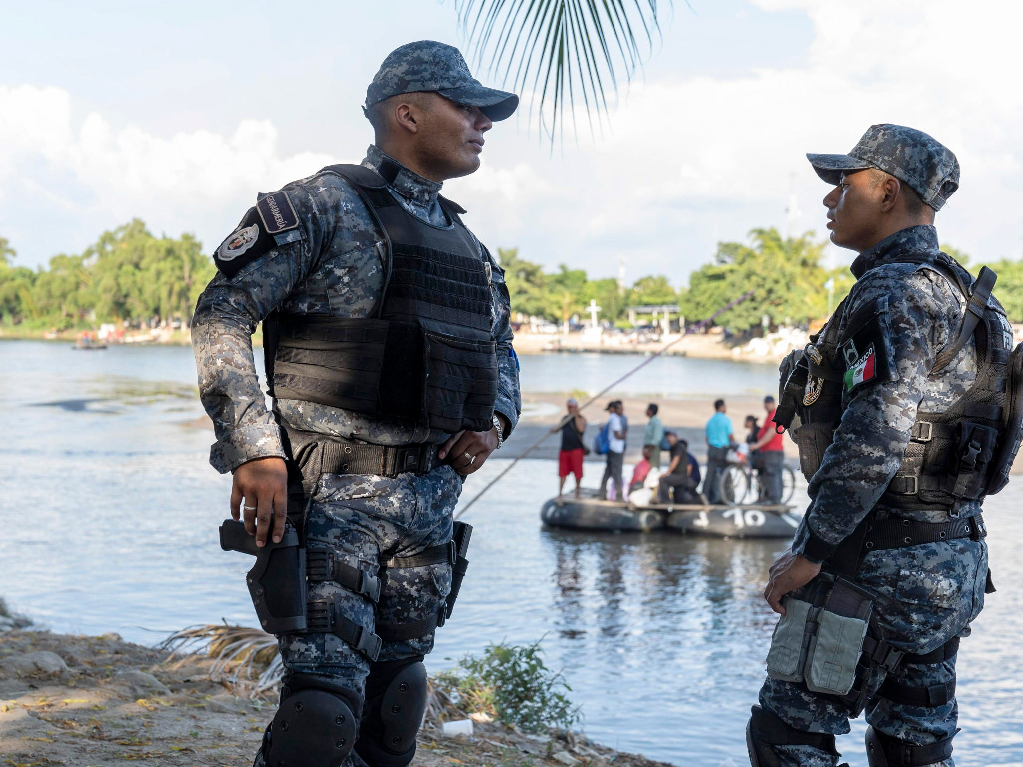 Mexican Federal Police and Immigration officers wait to check identification of the border crossers from Guatemala, who were crossing in a raft at Cuidad Hidalgo, Mexico on Oct. 25, 2018.