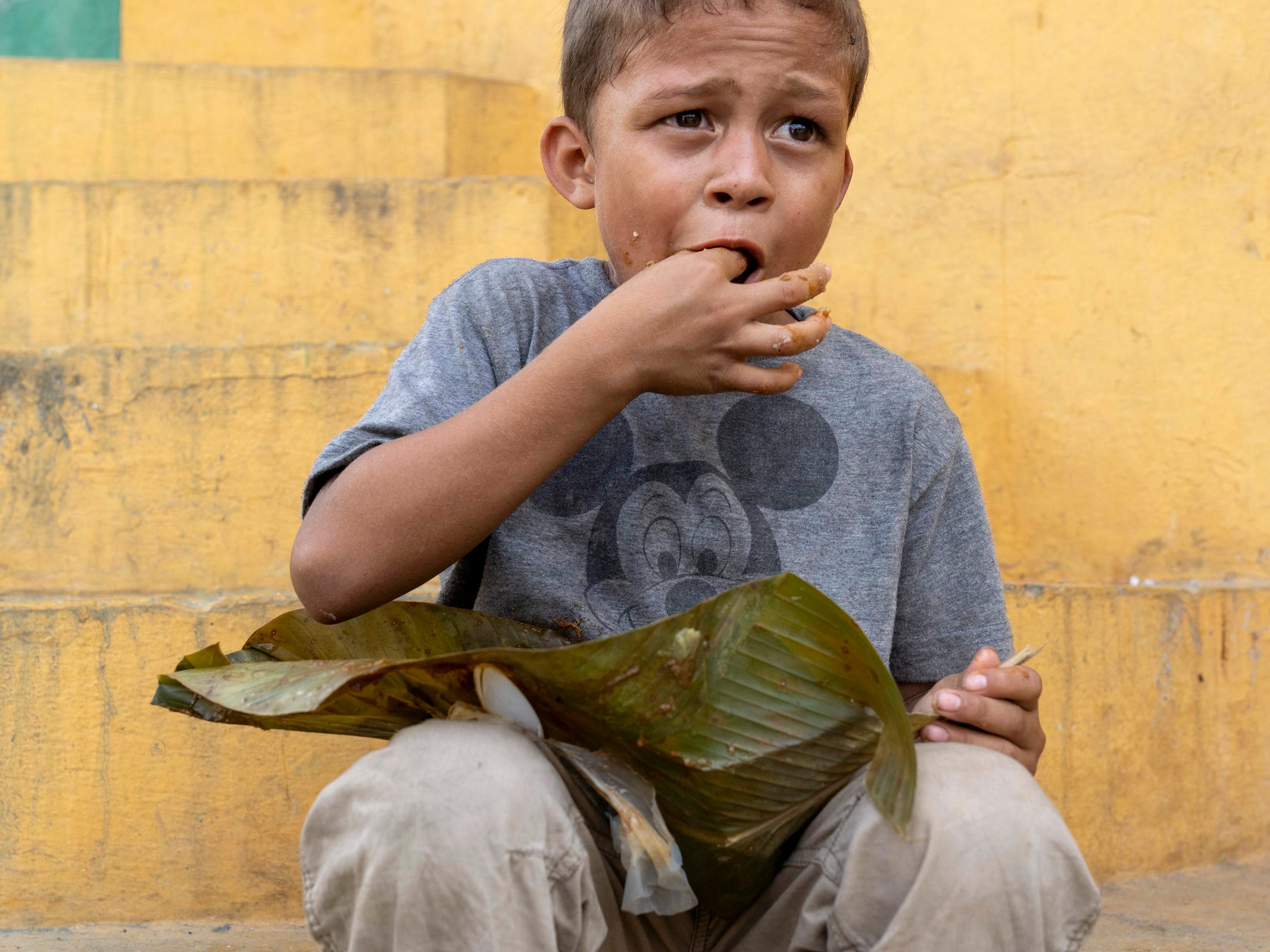 Gerson de Jesus Zelaya, 6, from Honduras, eats a donated lunch near a park in Tecum Uman, Guatemala as he waits to cross from Guatemala to Mexico and to head north to the United States on Oct 25, 2018.