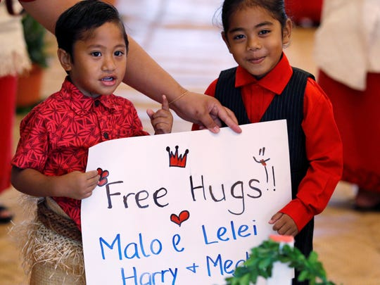 The children hold a sign while waiting for the arrival of Meghan, Duchess of Sussex and Prince Harry, Duke of Sussex, for their meeting with Tonga's Prime Minister in Nuku & alofa, Tonga, on Friday, October 26, 2018.