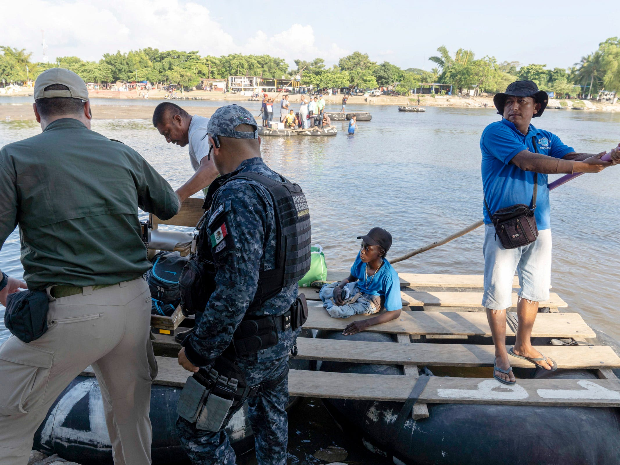 Mexican Federal Police and Immigration officers check identification of the border crossers from Guatemala, who were crossing in a raft at Cuidad Hidalgo, Mexico on Oct. 25, 2018.