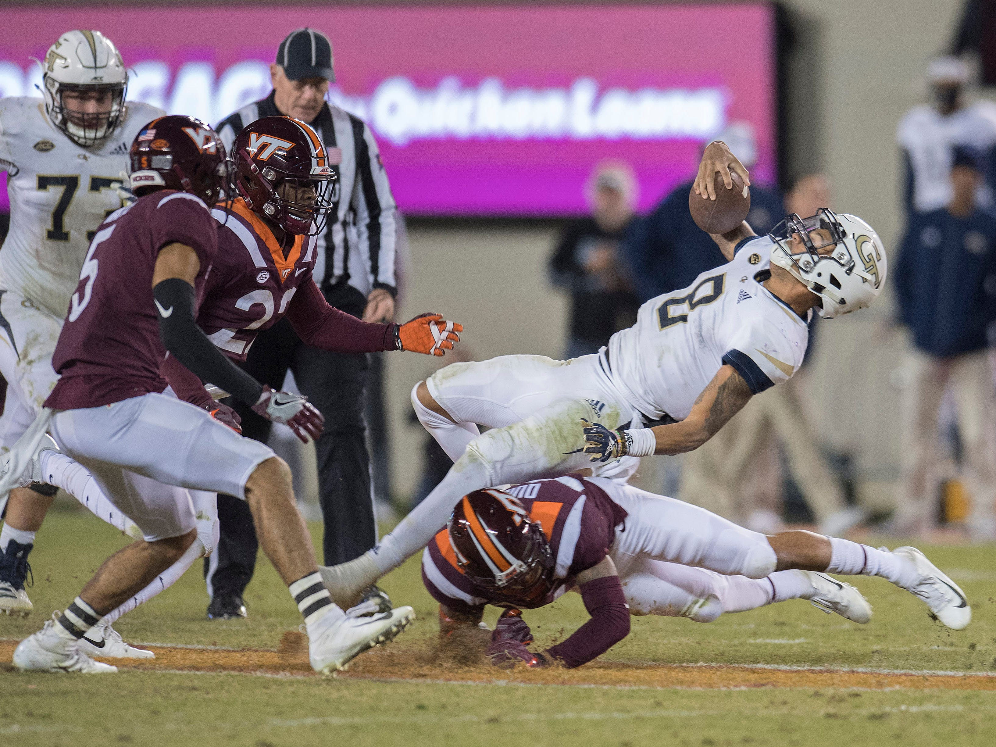 Georgia Tech quarterback Tobias Oliver (8) gets tackled by Virginia Tech defenders in the second half at Lane Stadium.