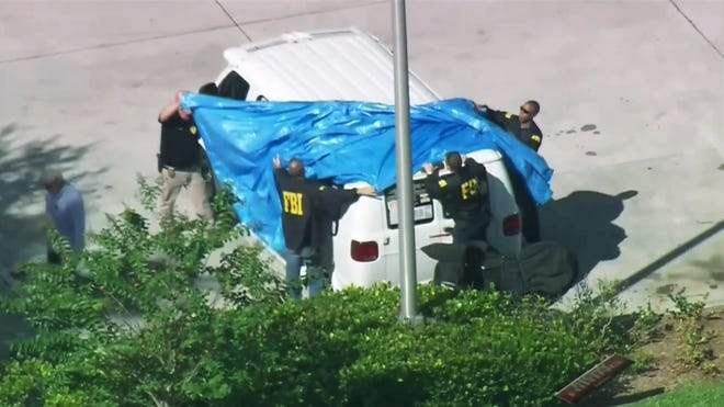 In this frame grab from video provided by WPLG-TV, FBI agents cover a van parked in Plantation, Fla., on Oct. 26, 2018, that federal agents and police officers have been examining in connection with package bombs that were sent to high-profile critics of President Donald Trump. The van has several stickers on the windows, including American flags, decals with logos and text.