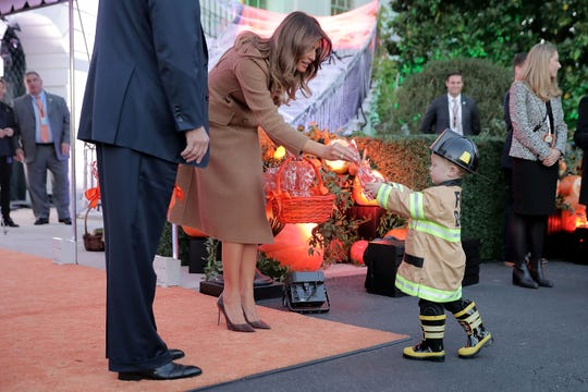 First lady Melania Trump gives a cookie to little trick-or-treater while hosting her first Halloween at the White House on the South Lawn, Oct. 30, 2017.
