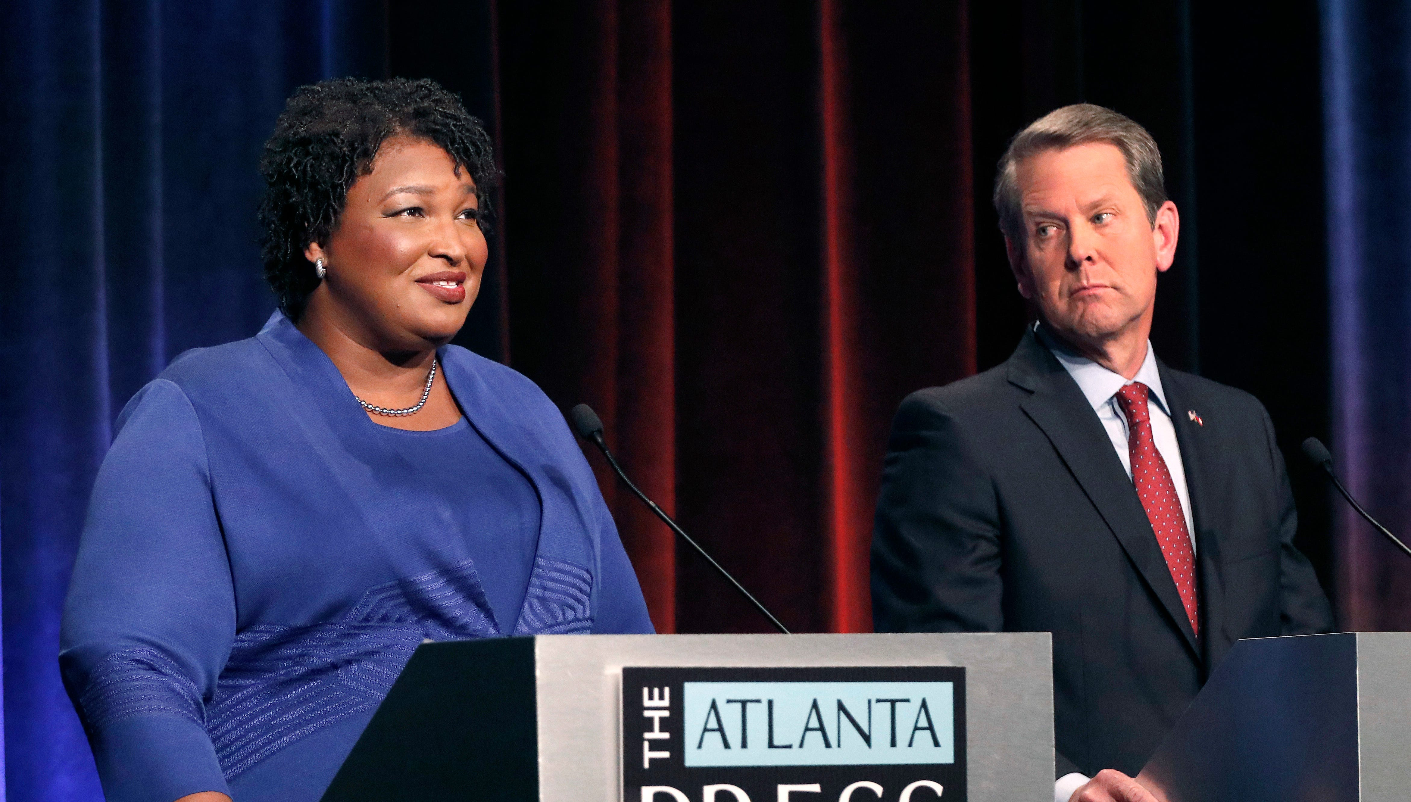 In this Tuesday, Oct. 23, 2018 file photo, Democratic gubernatorial candidate for Georgia Stacey Abrams, left, speaks as her Republican opponent Secretary of State Brian Kemp looks on during a debate in Atlanta.