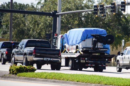 A van covered in blue tarp is towed by FBI investigators on October 26, 2018, in Plantation, Florida, in connection with the 12 suspicious packages mailed to top Democrats.