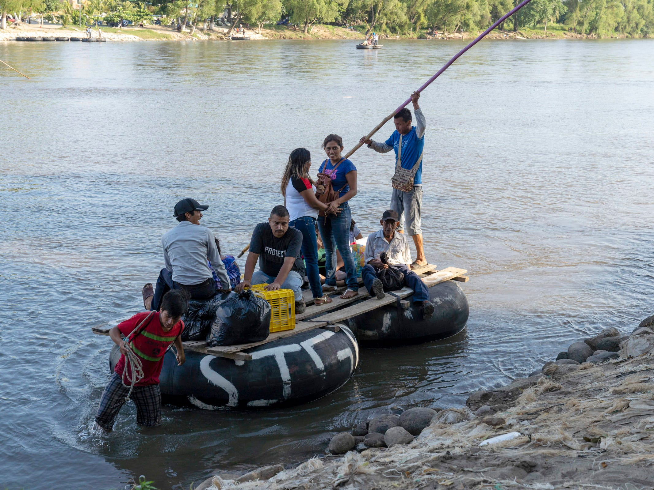 Border crossers from Guatemala, use a raft at cross the border into Mexico at Cuidad Hidalgo on Oct. 25, 2018.