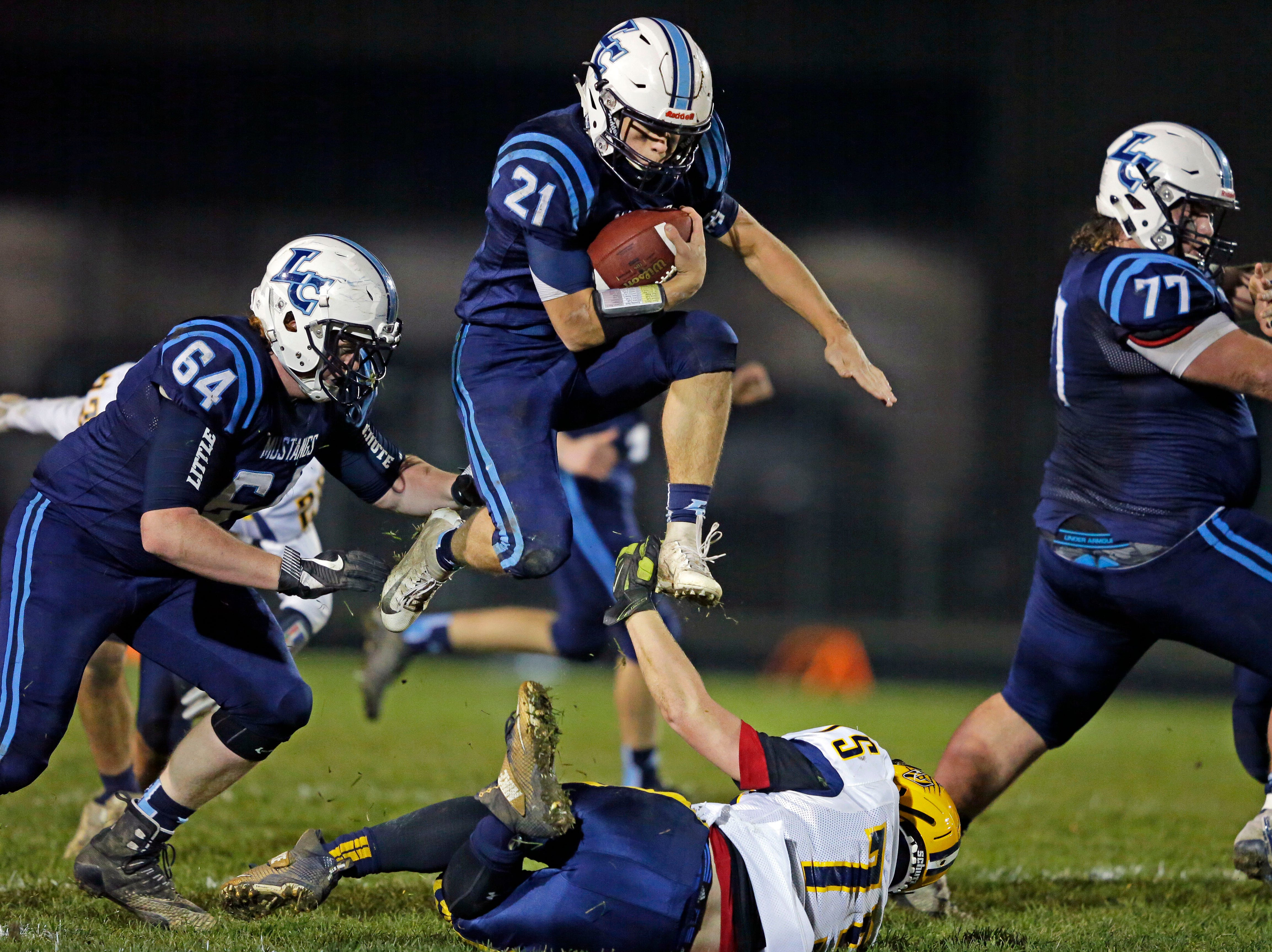 Isaac Van Deurzen of Little Chute leaps over Benjamin Savage of Chilton in a WIAA Division 4 second round football playoff game Friday, October 26, 2018, at Little Chute High School in Little Chute, Wis.Ron Page/USA TODAY NETWORK-Wisconsin