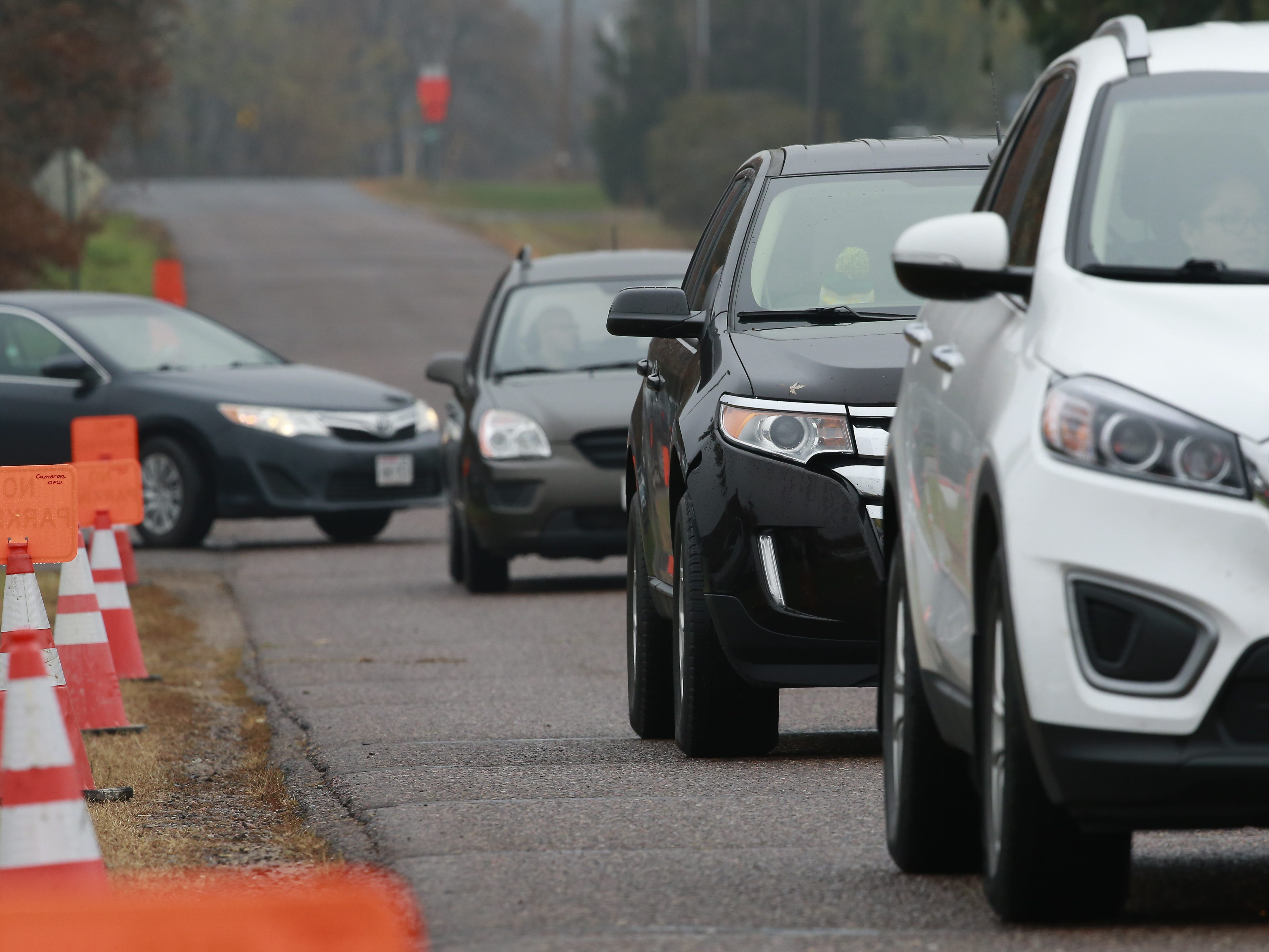 A line of cars leaves the visitation of James and Denise Closs on Saturday at St. Peter Catholic Church in Cameron. The couple was found dead in their Barron home on Oct. 15, and their deaths have been ruled homicides. Their 13-year-old daughter, Jayme, remains missing and is considered endangered.