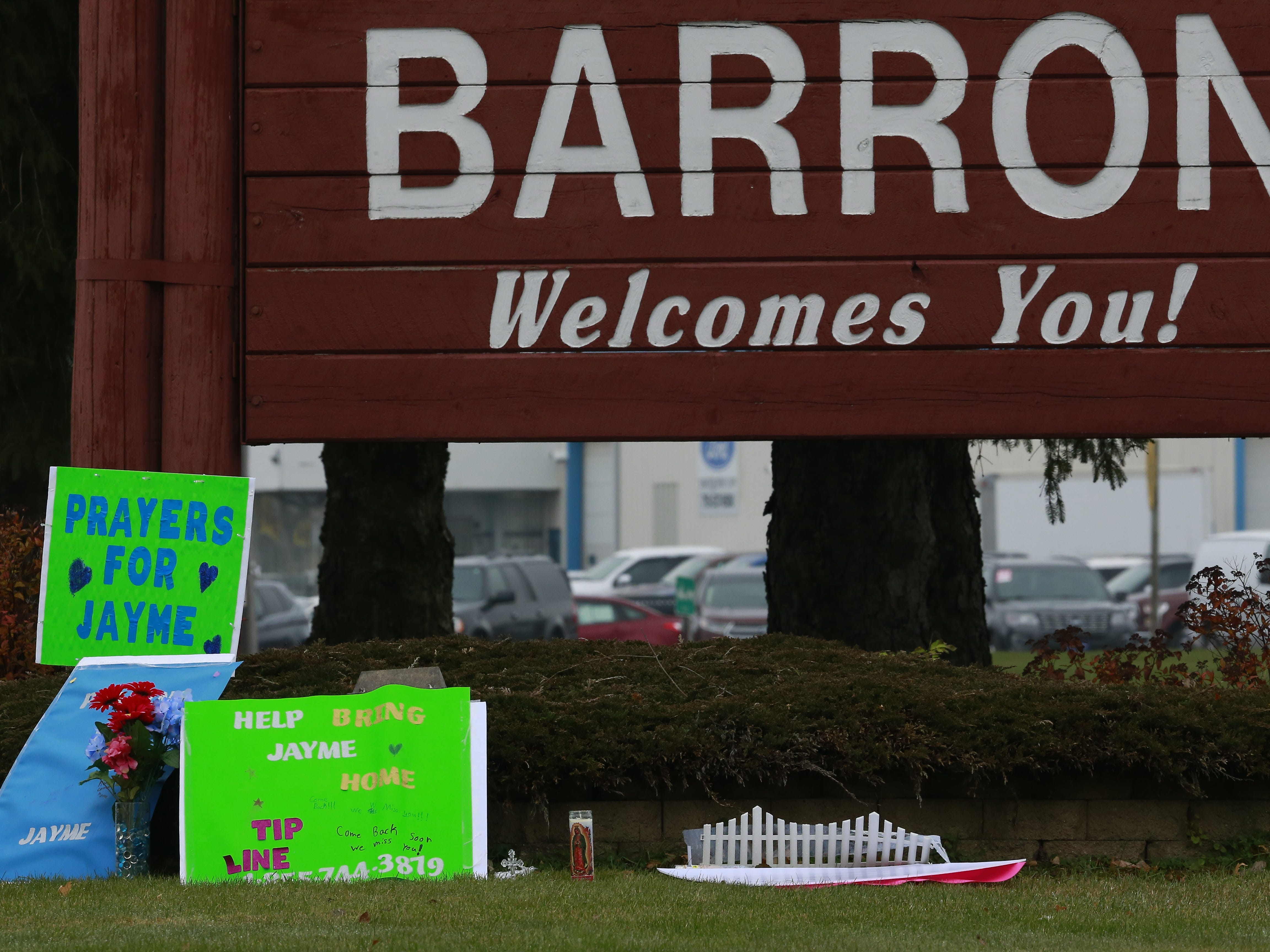 "Signs and flowers placed under the ""Barron Welcomes You!"" sign on Saturday reference the urgent efforts to find 13-year-old Jayme Closs, who has been missing since Oct. 15. Early that morning, her parents James and Denise Closs were found dead in their Barron home, and their deaths have been ruled homicides. Jayme has been missing ever since and is considered endangered."