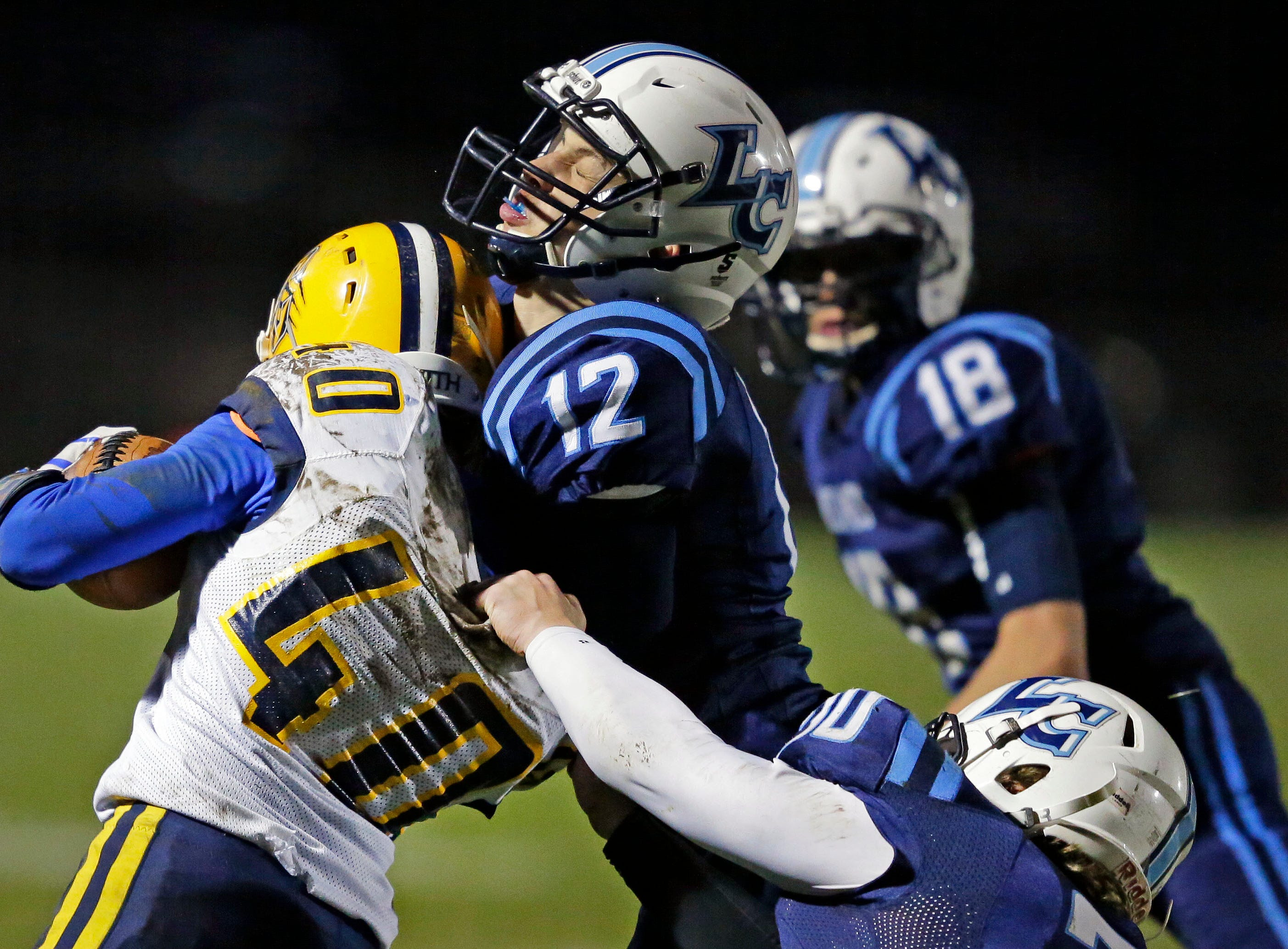 Cayden Popp of Chilton is tackled by Tate Huss (12) and Ryan Verstegen of Little Chute in a WIAA Division 4 second round football playoff game Friday, October 26, 2018, at Little Chute High School in Little Chute, Wis.Ron Page/USA TODAY NETWORK-Wisconsin