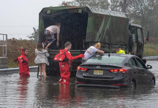Giselle Scalzo, Port Monmouth, emerges from the back seat of the car as she and Jessica Hirsch, (starting up the ladder) Port Monmouth, and Abby Cimmino, (entering the truck) Red Bank, had to be rescued on Wilson Ave, Port Monmouth. Their car was stuck in high water. Not pictured is Abby's brother Tyler Cimmino, Red Bank, who was also in the car. At far left is Port Monmouth firefighter Nick Quiles and at center is firefighter Lt. Robert Svenson, Jr. Person at right is unidentified. A nor'easter storm brought heavy rain, wind and flooding to Monmouth County Saturday, October 27, 2018.