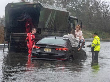 Jessica Hirsch (back to camera) Port Monmouth, emerges from the back seat of the car as she, Abby Cimmino, Red Bank, and two others not pictured, had to be rescued on Wilson Ave, Port Monmouth. Their car was stuck in high water. At left is Port Monmouth firefighter Lt. Robert Svenson, Jr. Person at right is unidentified. A nor'easter storm brought heavy rain, wind and flooding to Monmouth County Saturday, October 27, 2018.