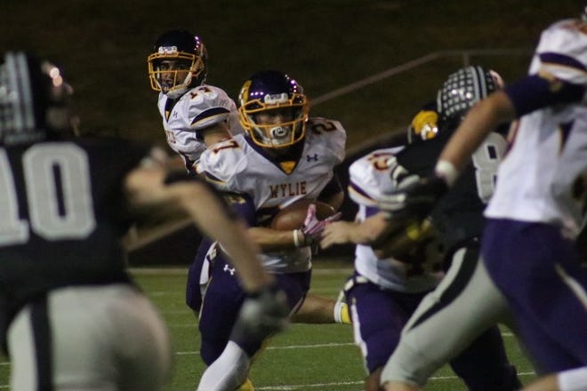 Wylie tailback Bailey Hicks (27) goes through a hole during Friday's game at Canyon Randall.