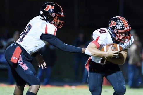 Pisgah quarterback Korey Griffith hands the ball to Jon Mehaffey Oct. 26, 2018 at Franklin. Pisgah won, 21-14.