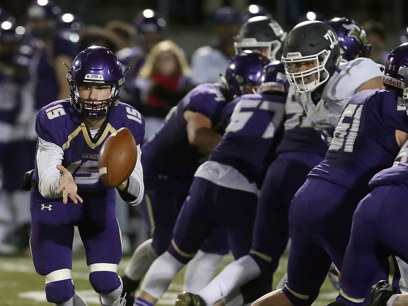 North Kitsap quarterback Andrew Blackmore makes a shovel pass to Clayton Williams against Olympic in Poulsbo on Friday, October 26, 2018.