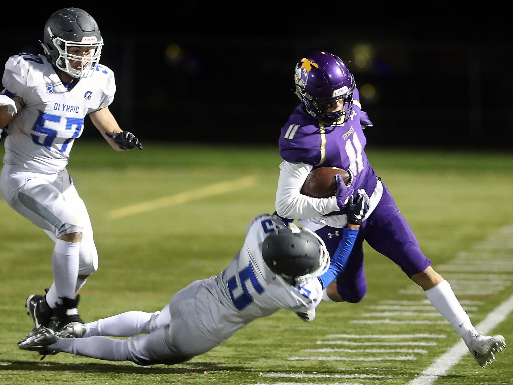 North Kitsap's John Jones (11) heads out of bounds as Olympic's Ethan Quitevis (5) tries to bring him downPoulsbo on Friday, October 26, 2018.