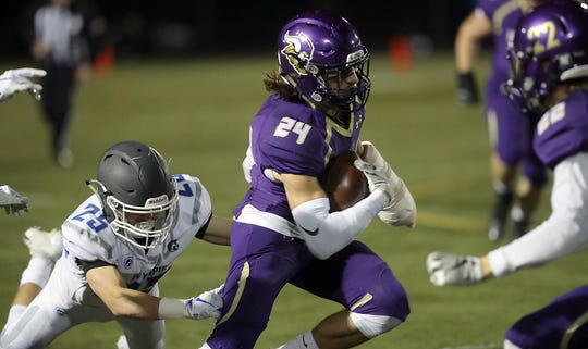Olympic's Taylor Andrews (25) tries to tackle Riley Solis of North Kitsap during the Vikings' 60-19 win Friday in Poulsbo.