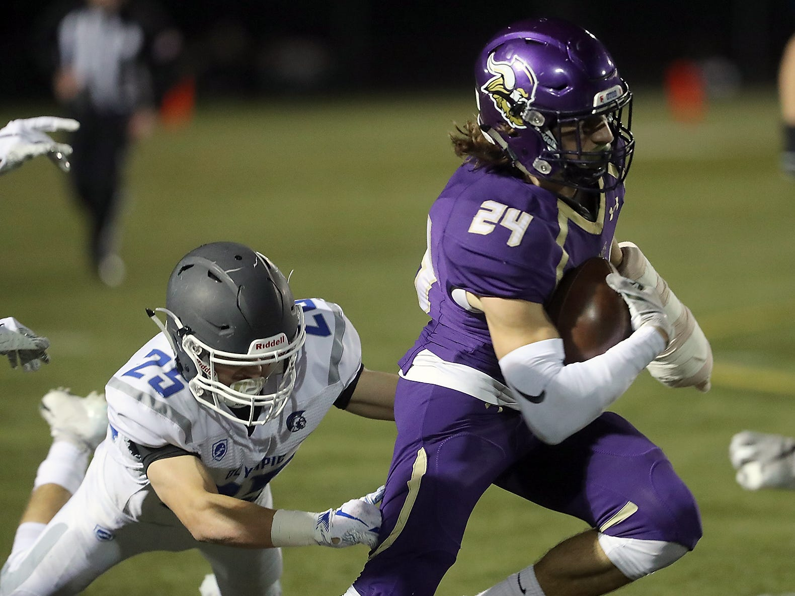 Olympic's Taylor Andrews (25) makes a grab for North Kitsap's Riley Solis (24) as he carries the ball down the field during the first half of their game in Poulsbo on Friday, October 26, 2018.
