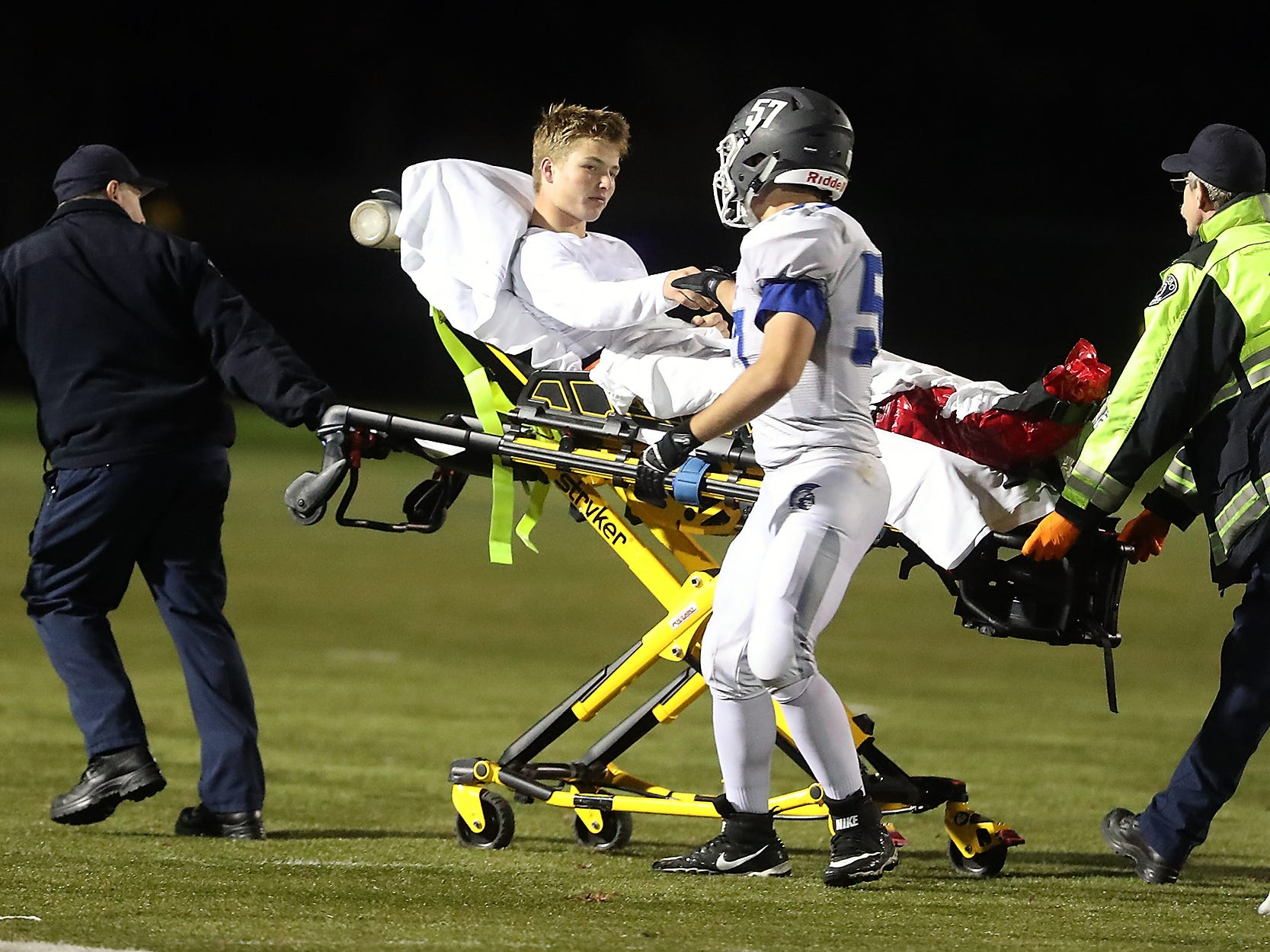 Olympic's Jonah Maatouk shakes hands with Colton Bower as Bower is wheeled off the field on a stretcher by the Poulsbo Fire Department after a hard hit during the first half of their game on Friday, October 26, 2018.