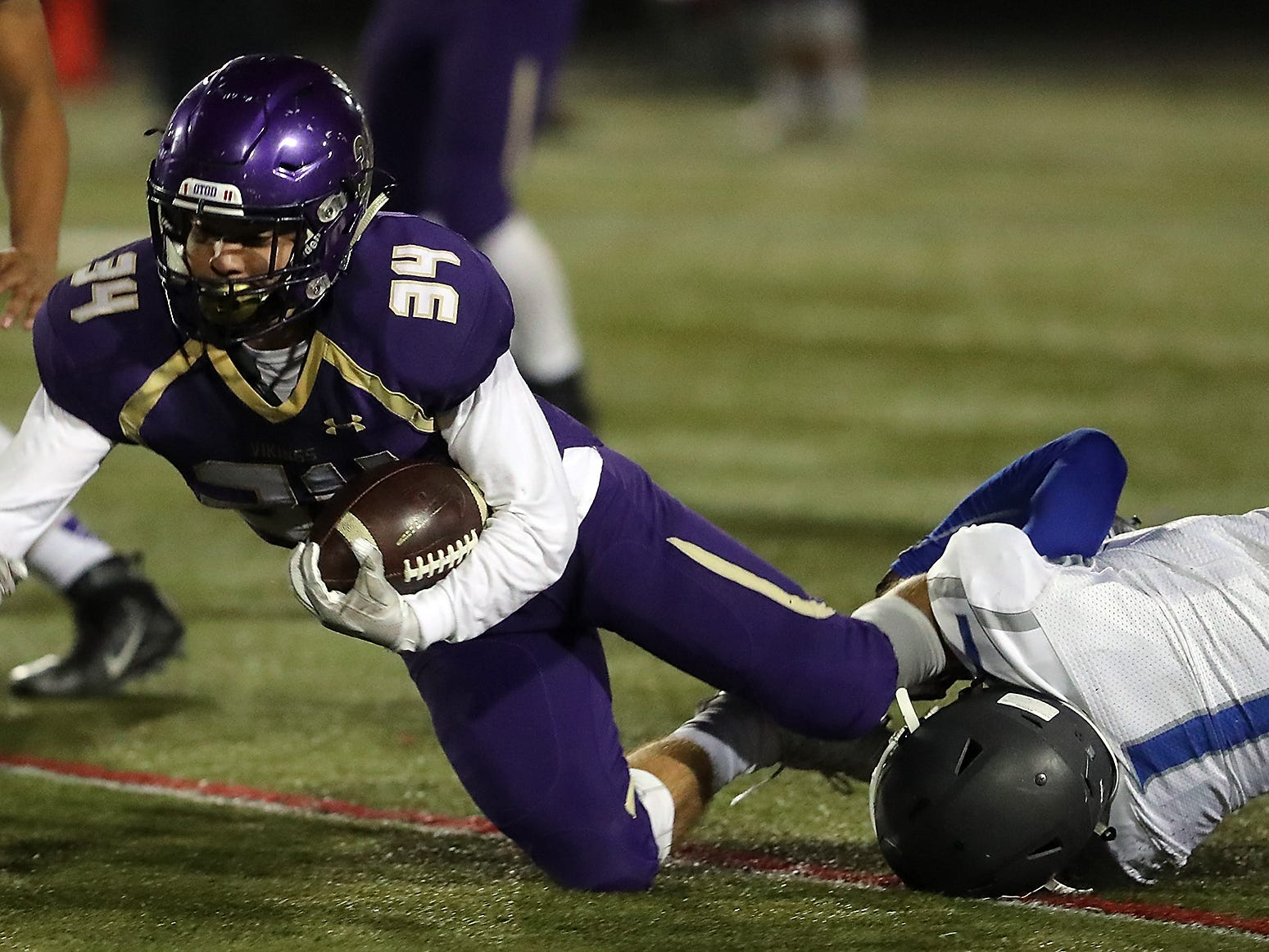 North Kitsap's Clayton Willilams (34) is brought down by Olympic's Malcolm Dewalt (1) during the first half of their game in Poulsbo on Friday, October 26, 2018.