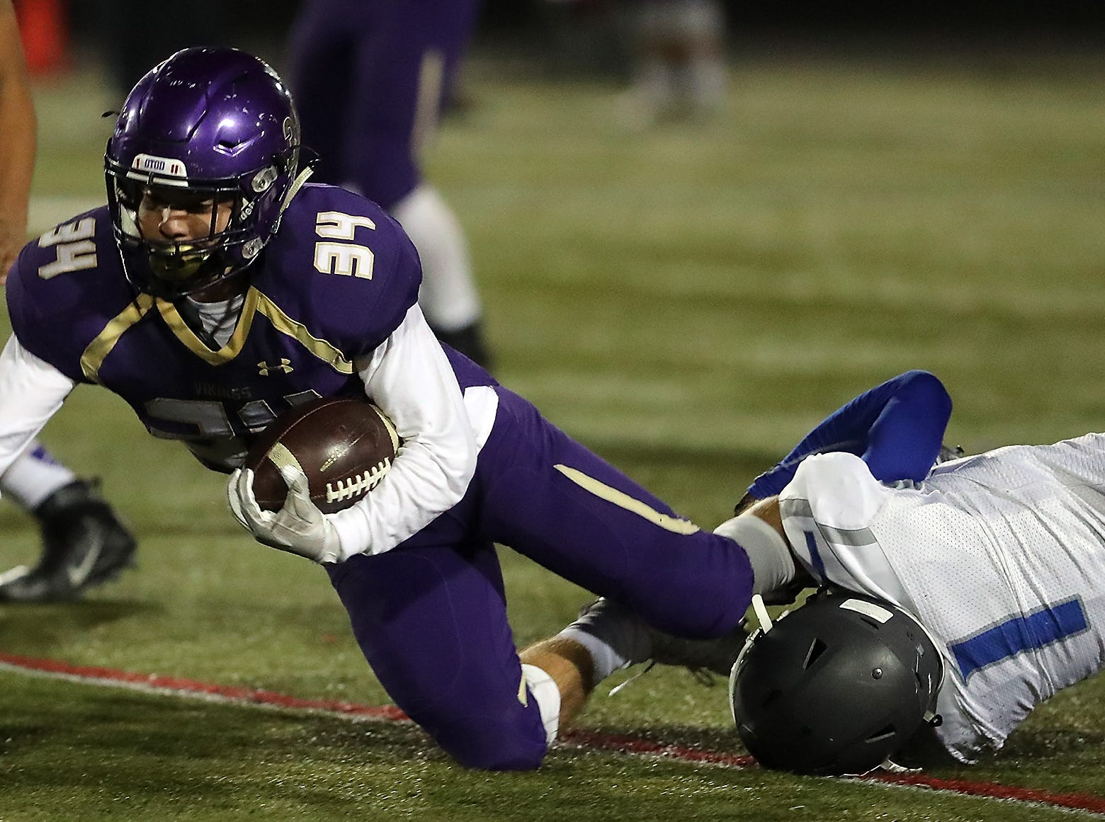 North Kitsap's Clayton Willilama (34) is brought down by Olympic's Malcolm Dewalt (1) during the first half of ther game in Poulsbo on Friday. Williams scored three touchdowns in the Vikings' 60-19 win.