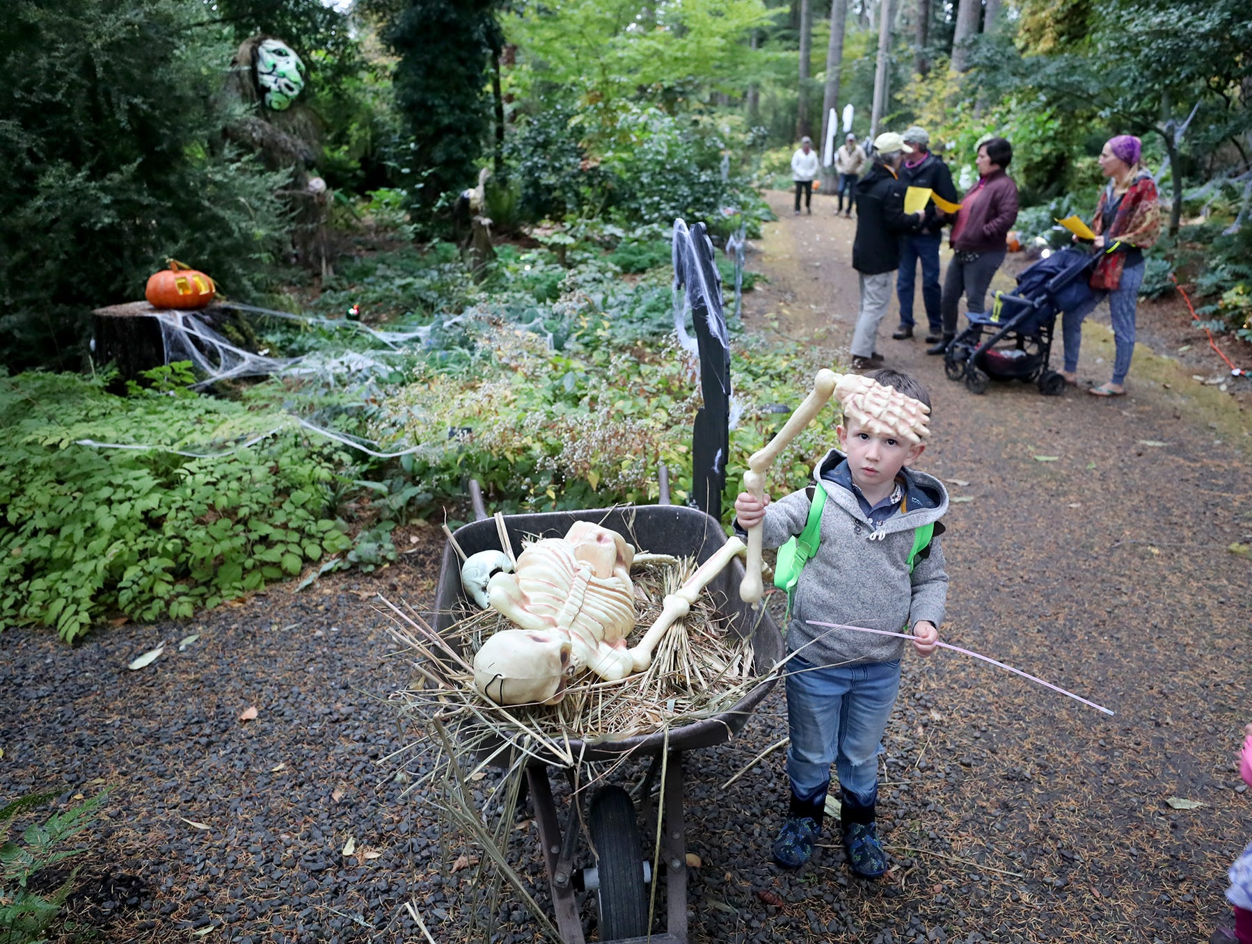 Eli Delp, 4, of Kingston lifts up an arm bone at the Haunted Heronswood 2018 in Kingston was Friday and Saturday, October,26-27. The second annual garden halloween charters tour featured some SÕKlallam folk stories.