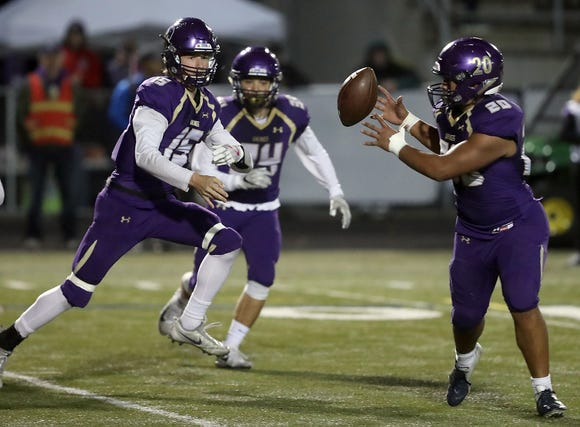 North Kitsap quarterback Andrew Blackmore shovel passes to Isaiah Kahana against Olympic in Poulsbo on Friday, October 26, 2018.
