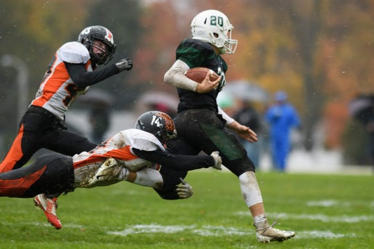 Middlebury's Tyler Buxton (14) tackles Rice's Ryan Byrnes (20) during the boys high school football game between the Middlebury Tigers and the Rice Green knights at Rice Memorial High School on Saturday afternoon October 27, 2018 in South Burlington.