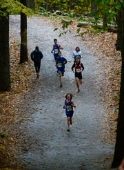 U-32's Jacob Miller Arsenault leads a pack of runners through the Woods Trail course during the Division II boys race at the Vermont State Championship Meet at Thetford Academy on Saturday, Oct. 27, 2018. The Raiders won the D-II boys team title.