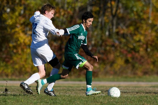Winooski's Lek Nath Luitel (2) runs past Vergennes' Kai Williams (22) with the ball during the boys soccer quarterfinal game between Vergennes and Winooski at Winooski High School on Friday afternoon October 26, 2018 in Winooski.