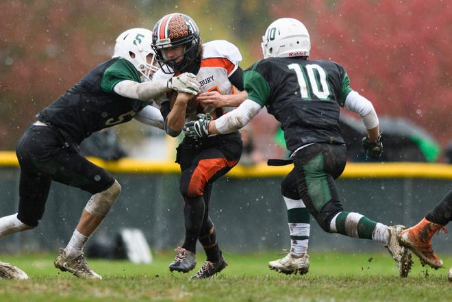 Middlebury's Simon Fischer (11) runs with the ball between Rice's Andrew Snell (5) and Cale Layman (10) during the boys high school football game between the Middlebury Tigers and the Rice Green knights at Rice Memorial High School on Saturday afternoon October 27, 2018 in South Burlington.