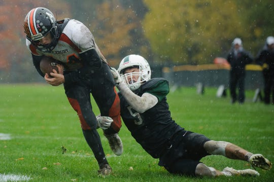 Rice's Andrew Snell (5) tries to tackle Middlebury's Tyler Buxton (14) during the boys high school football game between the Middlebury Tigers and the Rice Green knights at Rice Memorial High School on Saturday afternoon October 27, 2018 in South Burlington.