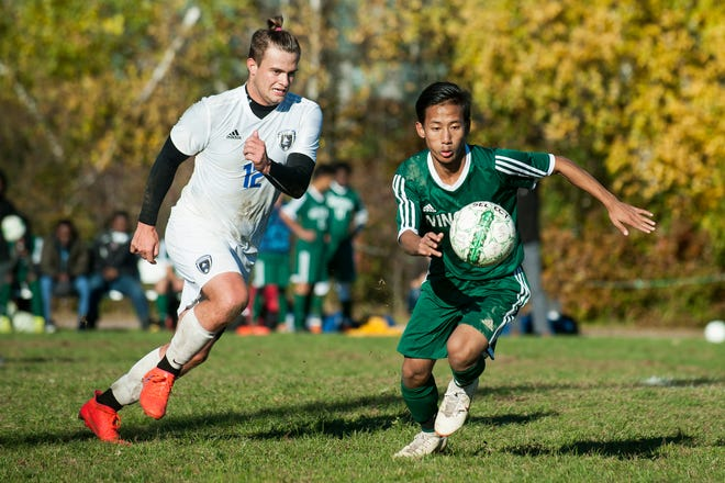 Vergennes' Nathan Wojciehowski (12) and Winooski's Bishal Limbu (7) chase down the ball during the boys soccer quarterfinal game between Vergennes and Winooski at Winooski High School on Friday afternoon October 26, 2018 in Winooski.