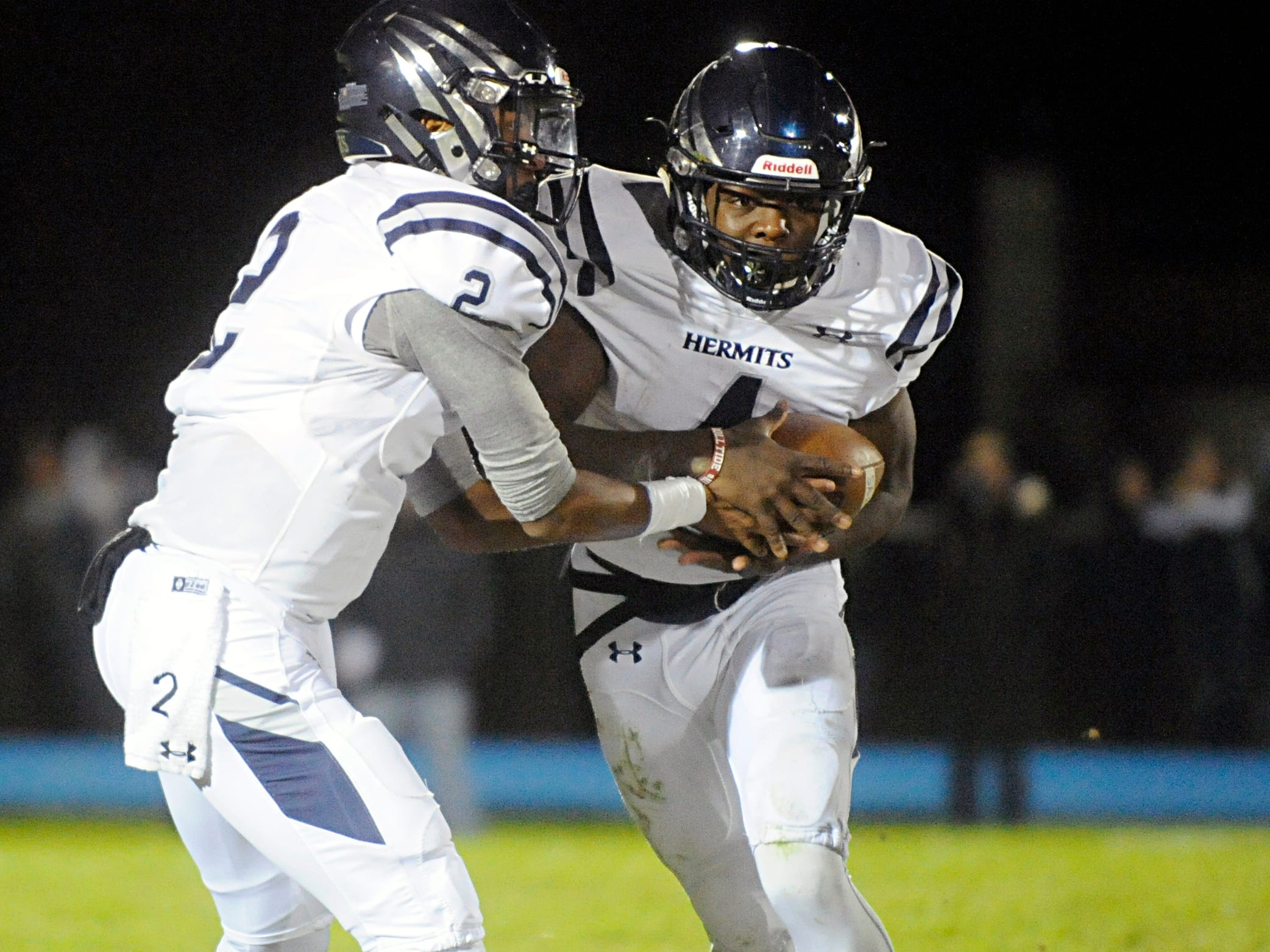 St. Augustine's QB Chris Allen hands the ball off to Nasir Hill during a game against Williamstown. The Braves topped the Hermits, 14-7, on Friday, October 26, 2018.