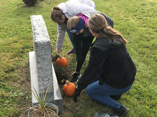 Emily Hamlin, Jessie Elick and Josey Williams work on cleaning up a grave site during a community service project conducted last week by the Adena Middle School National Junior Honor Society members.