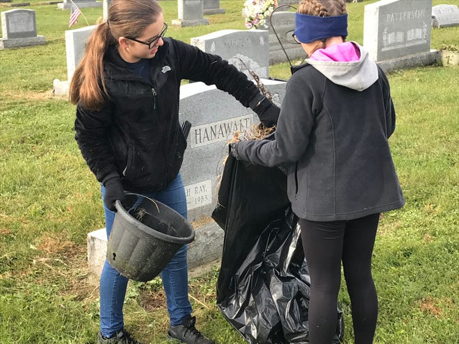 Josey Williams and Jessie Elick clear a dead potted plant from a grave site during a cleanup project conducted by Adena Middle School's National Junior Honor Society members last week.