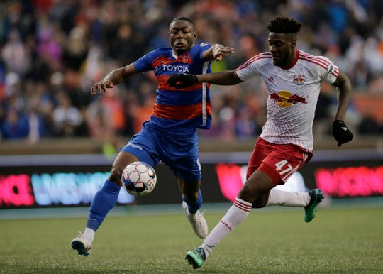 FC Cincinnati forward Fanendo Adi (9) and New York Red Bulls II defender Hassan Ndam (47) race to the ball in the second half of the USL Eastern Conference Semifinal match between the FC Cincinnati and the New York Red Bulls II at Nippert Stadium in Cincinnati on Tuesday, Oct. 16, 2018. FC Cincinnati was eliminated from the playoffs with a 1-0 loss to New York.