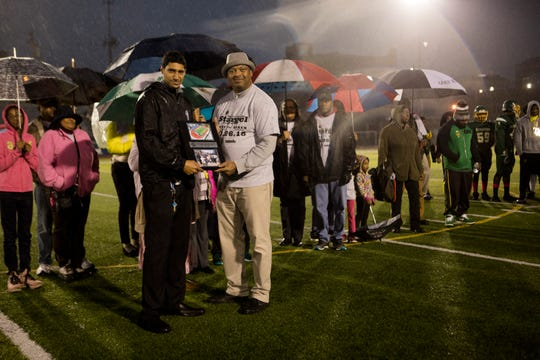 Josh Hardin, Cincinnati Public Schools Athletics director, gives Jason Stargel a plague in honor of his father before the OHSAA final regular season game between Taft High School and Aiken High School on Friday, Oct. 26, 2018 at Stargel Stadium in the West End.