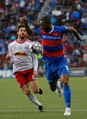FC Cincinnati forward Fanendo Adi (9) beats New York Red Bulls II midfielder Ethan Kutler (41) for the ball in the second half of the USL Eastern Conference Semifinal match between the FC Cincinnati and the New York Red Bulls II at Nippert Stadium in Cincinnati on Tuesday, Oct. 16, 2018. FC Cincinnati was eliminated from the playoffs with a 1-0 loss to New York.